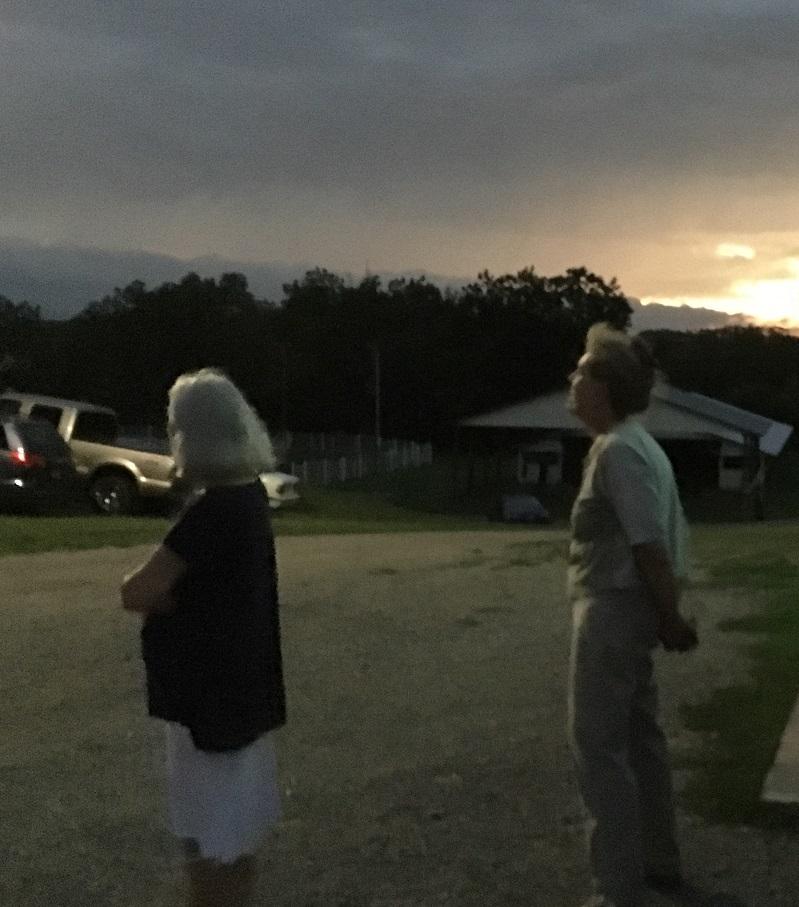 two older women standing beneath a dark sky